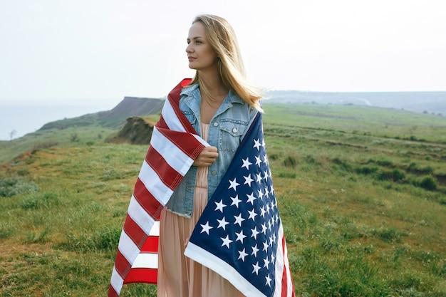 サンゴのドレスとデニムのジャケットを着た少女は、米国の旗を手に持っています。 7月4日の独立記念日。