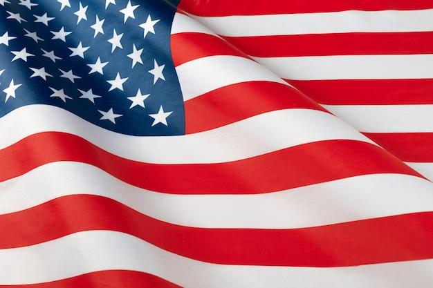 波立たせられたアメリカの国旗のクローズアップ。アメリカのサテンの質感の湾曲した旗。記念日または7月4日。バナー、自由の概念