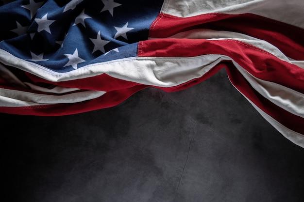 セメントの背景の上に横たわる米国旗。アメリカの象徴。 7月4日またはアメリカ合衆国の記念日