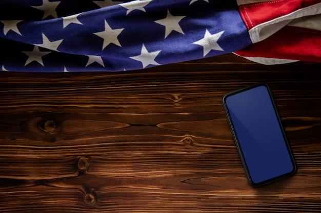 7月4日または米国の概念の記念日。モックアップ用の空白のモバイル画面。木製の背景の上に横たわる米国旗。アメリカの象徴。上面図