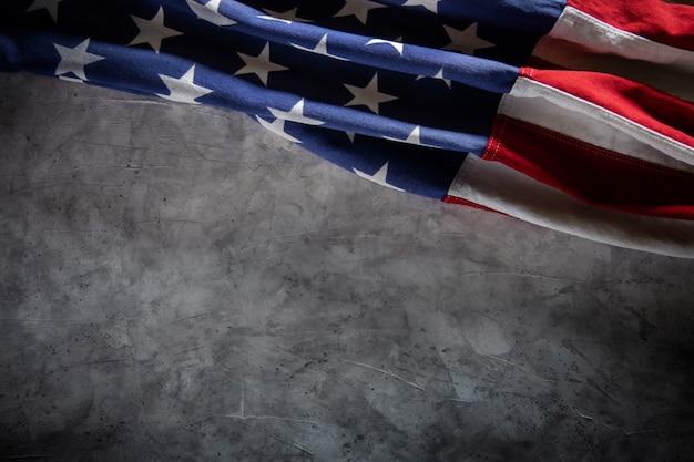 セメントの背景の上に横たわる米国旗。アメリカの象徴。 7月4日またはアメリカ合衆国の記念日。テキストのコピースペース