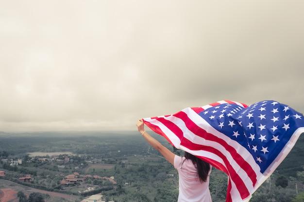 若い女性は、青い空を背景にアメリカ国旗を上げます。独立記念日、7月4日