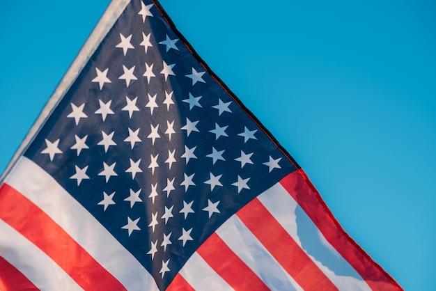 青い空にアメリカの国旗をクローズアップ。アメリカでの7月4日の独立記念日のシンボル