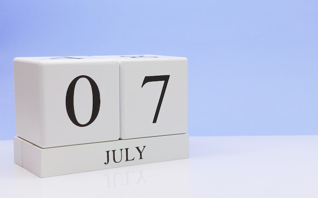 7月7日月の7日目、明るい青の背景と、反射と白いテーブルに毎日のカレンダー。