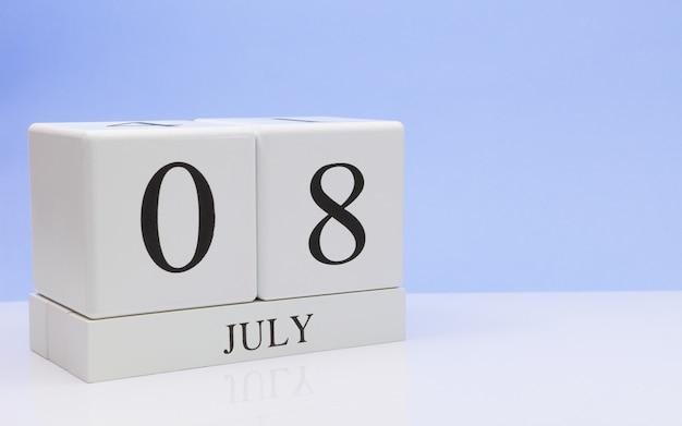 7月8日月の8日目、水色の背景で反射と白いテーブルの上の毎日のカレンダー。夏時間、テキスト用の空きスペース