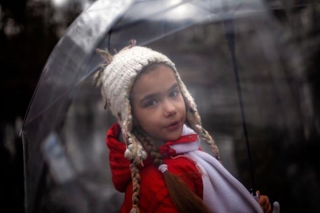Девочка 7-8 лет в красном пальто с прозрачным зонтиком гуляет одна в весеннем лесу