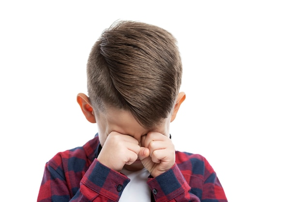 A 7-year-old boy cries and rubs his eyes with his hands. close-up. isolated on white wall.