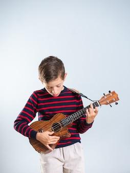 灰色の背景に分離されたウクレレを演奏する7歳の少年