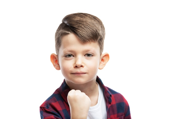 A 7-year-old boy shows his fist. close-up. isolated on white wall.