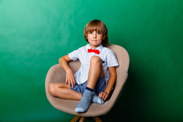 7-летний мальчик сидит на стуле в студии на зеленом фоне