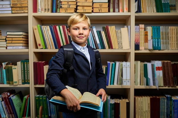 7 year old boy with book in school library, in formal school wear. diligent, intelligent and clever children engaged in studying