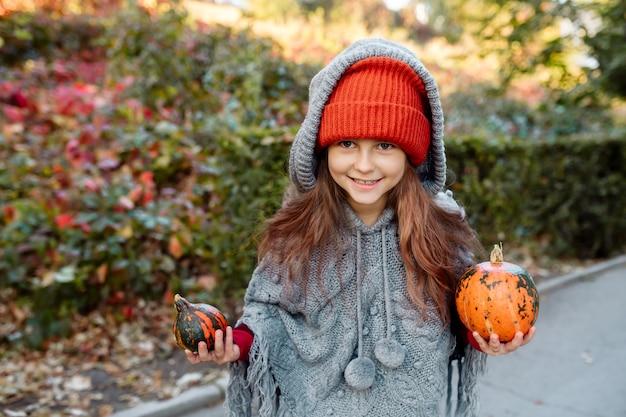 魔女として公園でポーズをとる2つのカボチャとハロウィーンのデザインの凝った服を着た7歳の少女