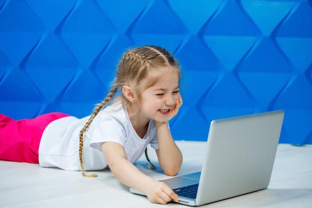 흰색 티셔츠를 입은 7세 소녀는 노트북을 들고 바닥에 앉아 키를 누릅니다
