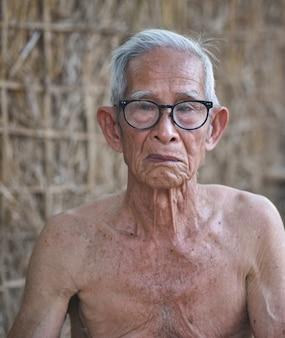 アジアの老人の顔高齢の深刻な男の中高年の肖像画非常に老人男性70から80歳脱いでいて眼鏡をかけています