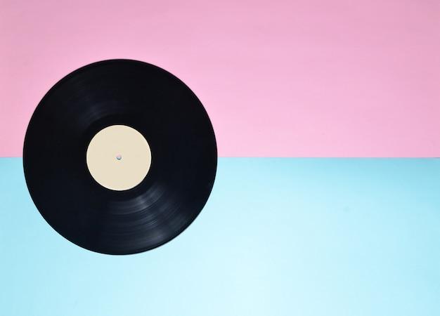 ブルーピンクのパステル調の背景にビニールプレート。ミニマリズムの傾向。 70年代のレトロなメディア。オーディオ技術。上面図。コピースペース。