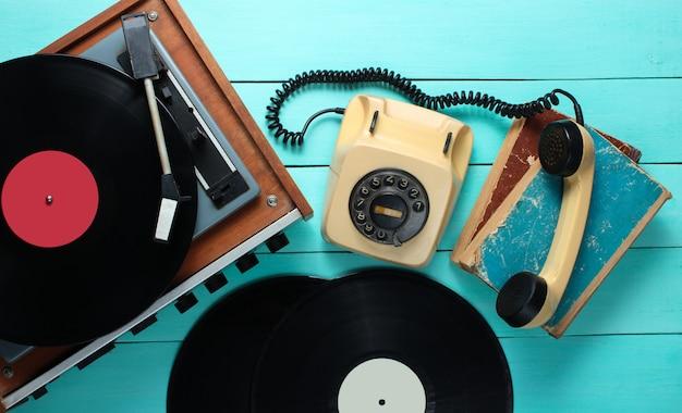 Виниловый проигрыватель, поворотный телефон, виниловые таблички, старые книги. старомодные объекты на синем фоне деревянные. стиль ретро, 70-е. вид сверху.