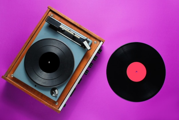 紫色の背景にビニールレコードとレトロな70年代のビニールレコードプレーヤー