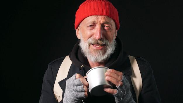 孤立した暗い背景にしわくちゃの顔を持つ70歳の男性のクローズアップの肖像画。暗い背景に彼の手で空のマグカップを持つホームレスの男性