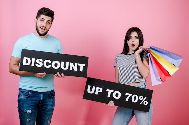 幸せな笑みを浮かべてハンサムなカップルの男性と女性最大70%の割引記号とカラフルなショッピングバッグ