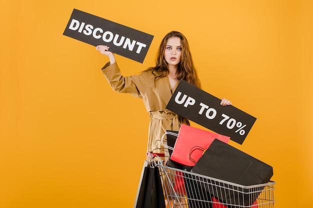 若い女性は、ショッピングバッグと黄色で分離された信号テープの完全なカートで最大70%の割引を持っています
