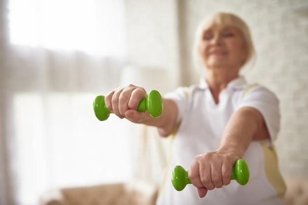 ダンベル運動70歳の女性運動をしています。