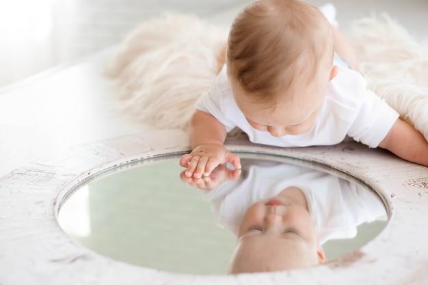 7ヶ月の小さな男の子が寝室の白いカーペットで遊ぶ