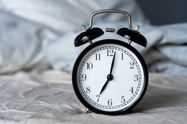 ベル付きのスタイリッシュな目覚まし時計。手は7時間を示しています。起床時間