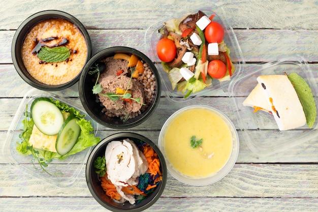 7つの食品容器で食べる準備ができた食事。持ち帰り弁当からの健康的な食事。適切な栄養概念、フラットレイアウトの食品