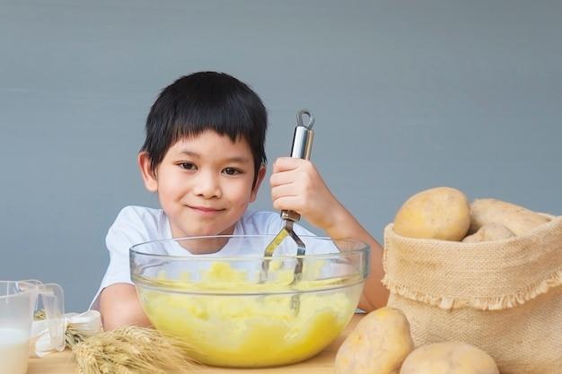 マッシュポテトを楽しく作る7歳の少年