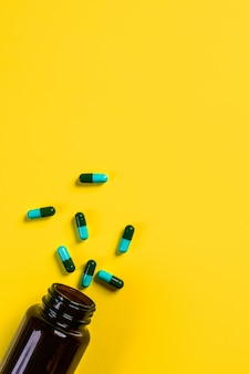 黄色の背景に茶色の透明な薬瓶から注がれた7つの青緑色のカプセル。薬理学の概念。