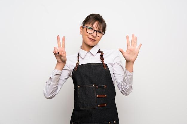 指で7を数えるエプロンを持つ若い女性