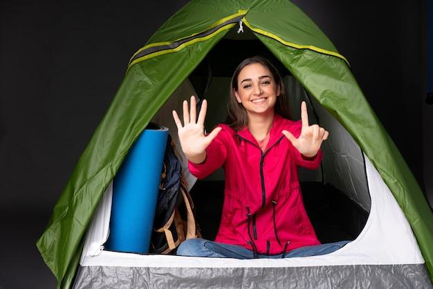 指で7を数えるキャンプの緑のテントの中の若い女性