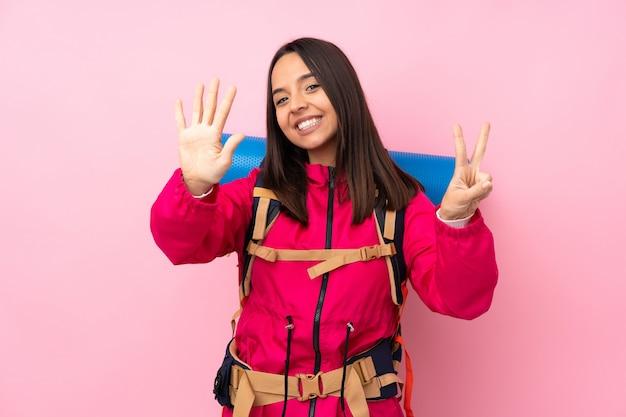 指で7を数える孤立したピンクの壁に大きなバックパックを持つ若い登山家女性