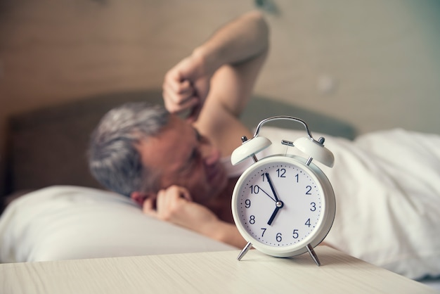 早朝の目覚まし時計で眠っている眠っている男。怒っている男は寝床で騒音で目を覚ます。起きた。朝の午前7時に目覚まし時計をオフにしてベッドに横たわっている男