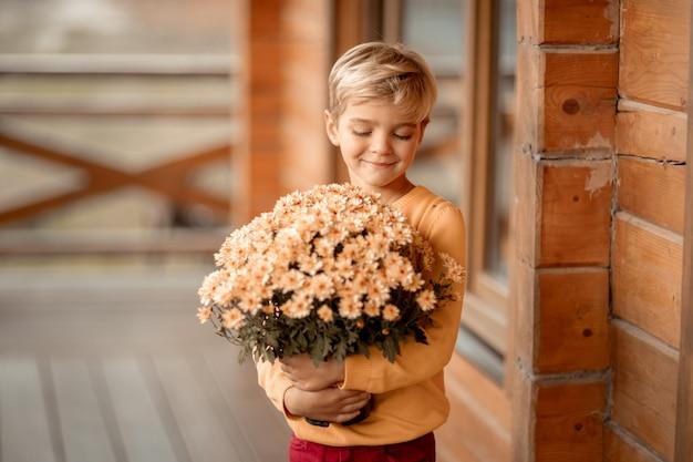 7歳の男の子が村の木造住宅の近くに花束を持っています。