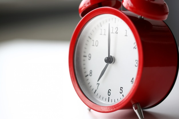 朝の7に設定された赤い目覚まし時計