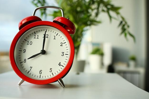 朝の7時に設定された赤い目覚まし時計