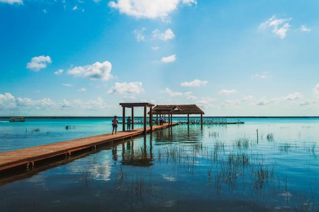 美しい風景と7色のラグーンの木製の桟橋。メキシコ、キンタナロー州のバカラルラグーンの透明な水を楽しむ人々