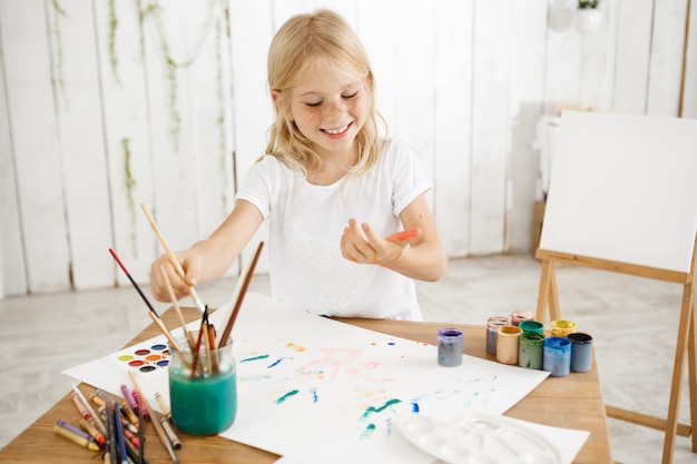 テーブルの上に横たわる白い紙の上にペンキを滴下する金髪の7歳の女の子が歯を浮かべて楽しんで、楽しく、楽しんでいます。楽しい、絵を楽しんでいる創造的な子供。