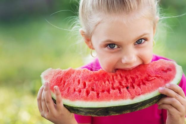 Маленькая милая девочка 7 лет ест арбуз