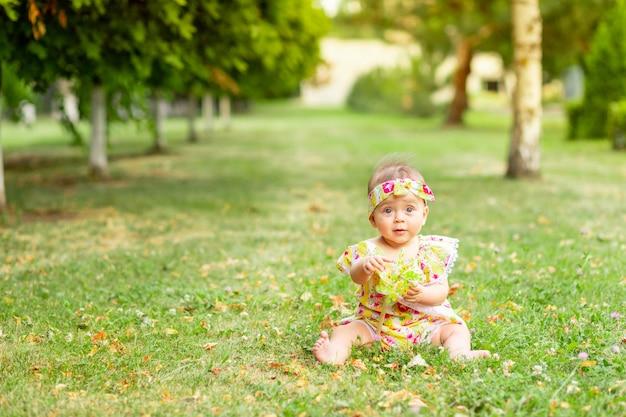 生後7ヶ月の黄色のドレスの緑の芝生の上に座って、おもちゃで遊ぶ小さな女の赤ちゃん