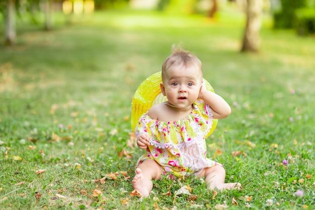 7か月の小さな女の赤ちゃんが黄色のドレスと帽子の緑の芝生に座って、彼女の耳に手をかざしています。