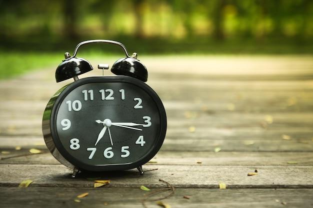 黒い目覚まし時計木の床で午前7時に教えてください。