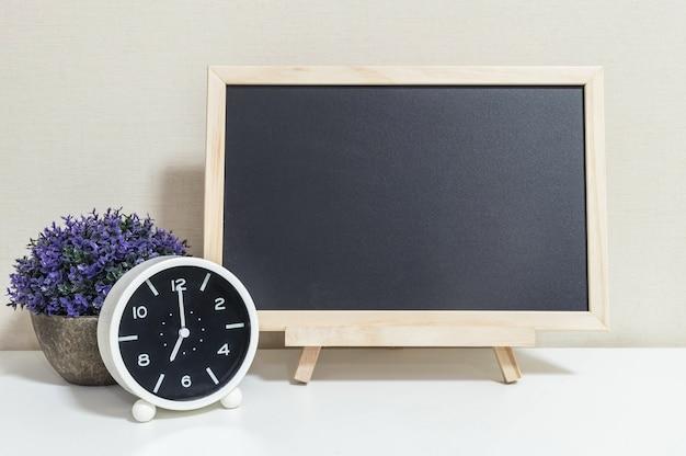クローズアップの目覚まし時計ショー7時の机の上の木の黒板