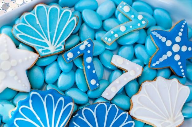 青いアイシング、シェルのようなクッキー、星、7番のチョコレート菓子でいっぱいの白いシェルプレート