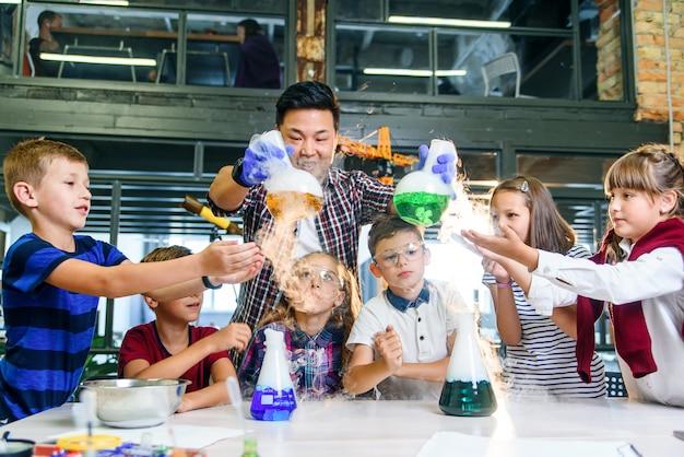 Азиатский молодой учитель с группой из шести веселых кавказских учеников 8-10 лет, носящих защитные очки во время химического эксперимента с цветными жидкостями в современной школе.