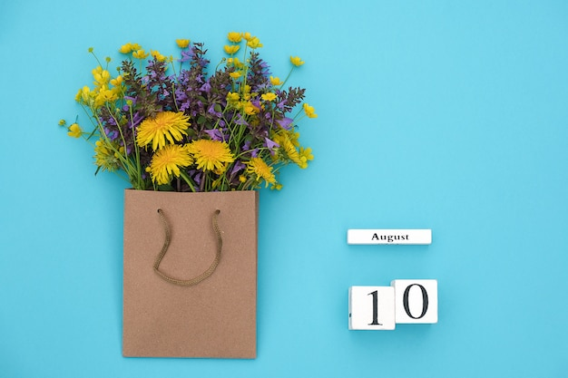木製キューブカレンダー8月10日と青のクラフトパッケージのフィールドカラフルな素朴な花