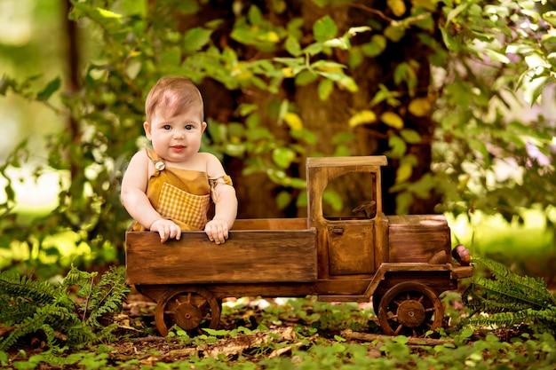 8〜12ヶ月の幸せな小さな幼児男の子は、自然の中で木製のベビーカーに座っています。