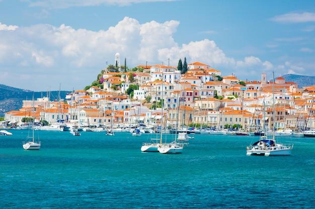 Порос, греция - 8-ое июня 2016: красивый вид чудесного портового города на предпосылке неба в греции