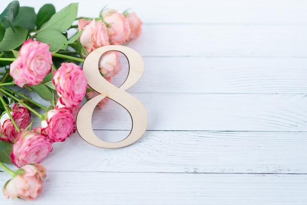 白いテーブルにピンクの花を持つ木製図8。国際女性の日。 3月8日